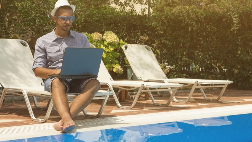 Guy working on laptop next to the swimming pool